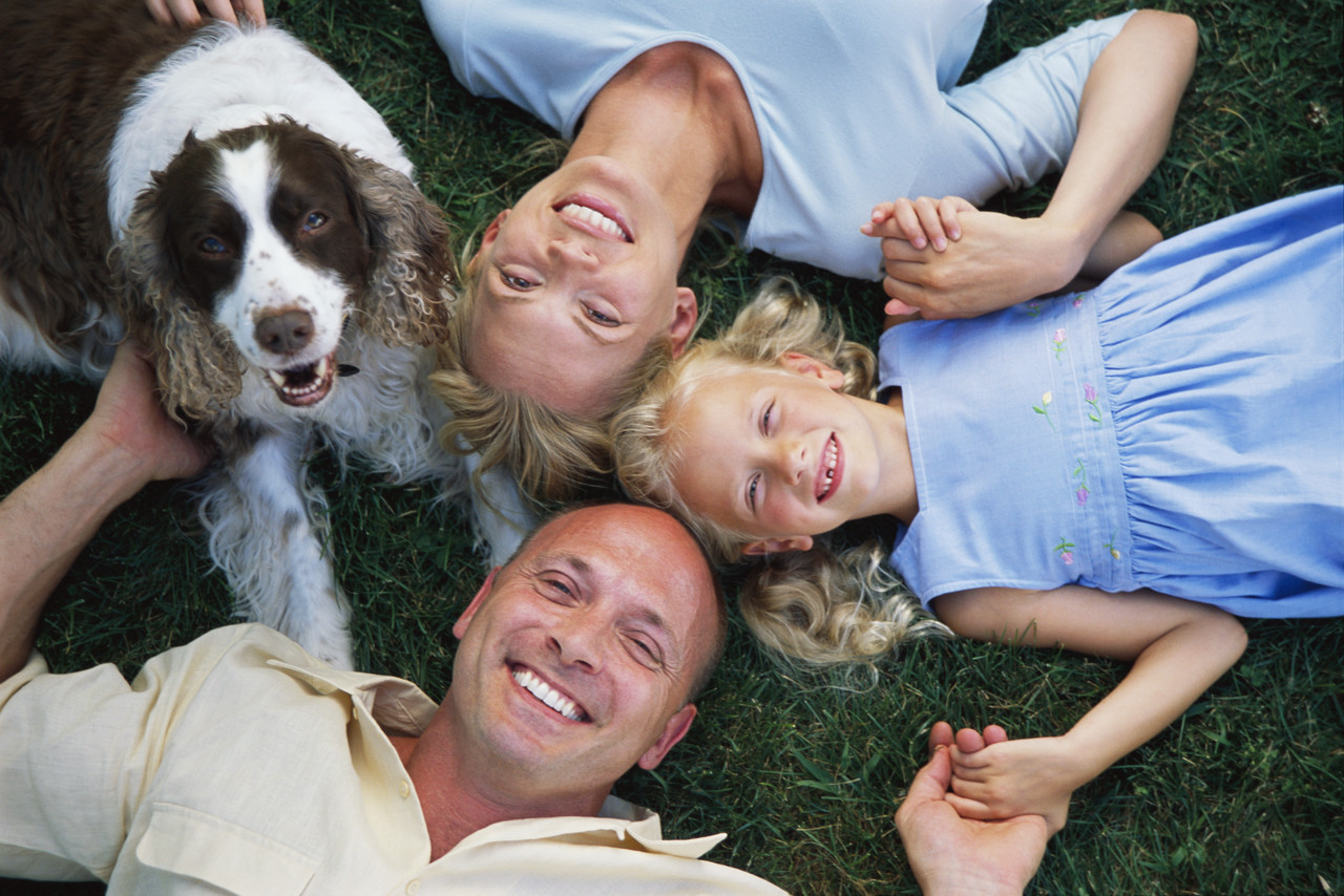 photo of a family and their dog lying on the the lawn on the what is estate planning and who needs estate planning page